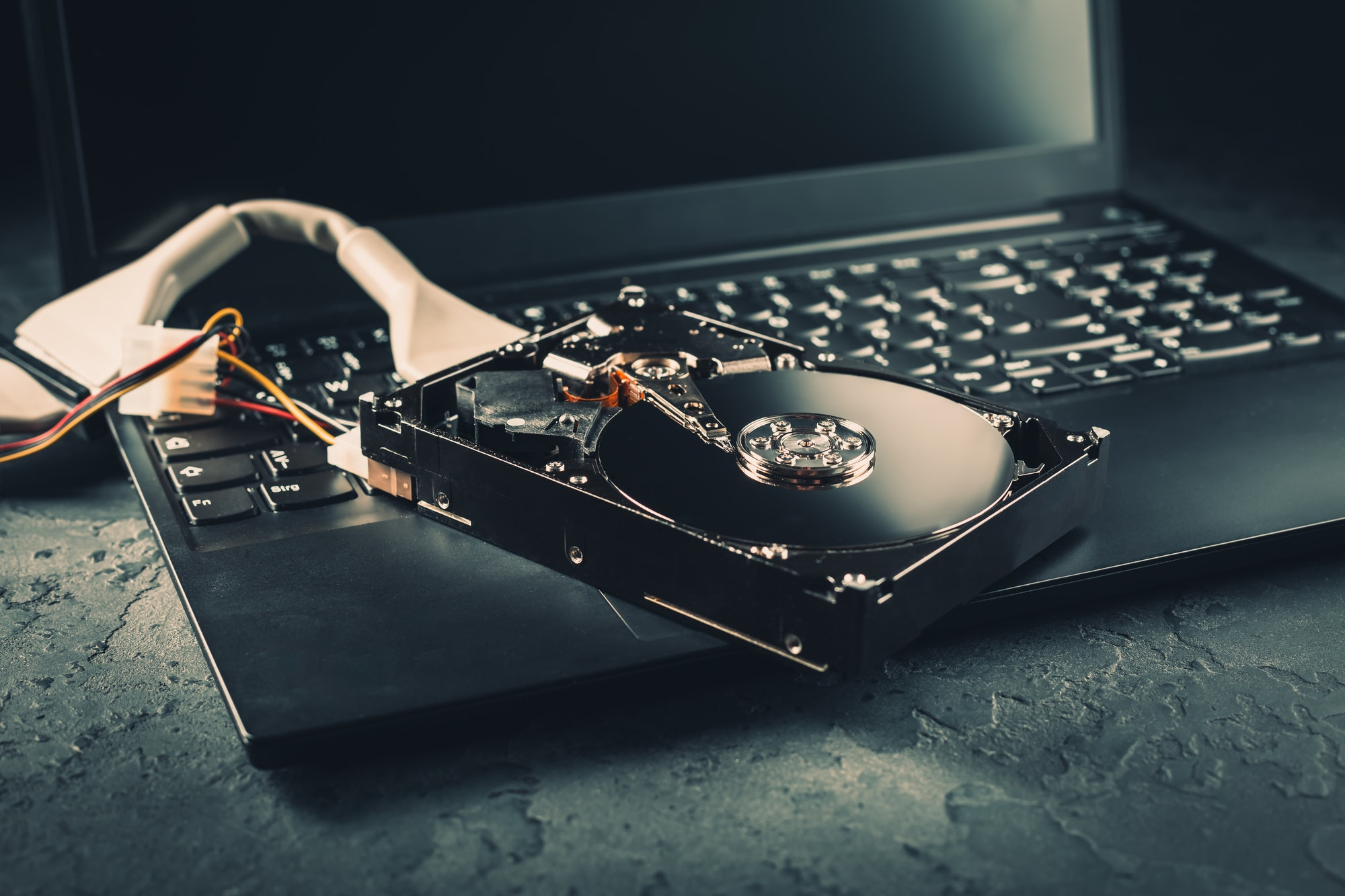 Open Hard drive on keyboard of laptop in dark tone